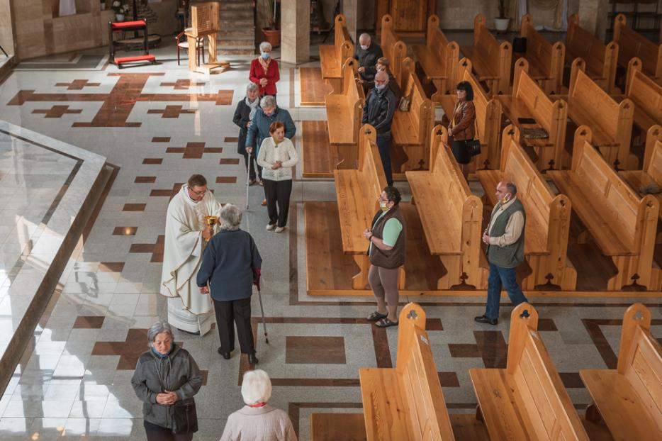 Parishioners social-distance while taking Communion amid the coronavirus pandemic in Lubin, Poland on May 21, 2020.