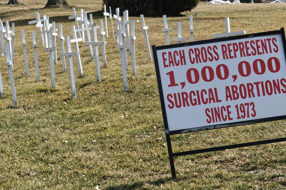 """White crosses in front of a church in Lansdale, PA on March 14, 2019 with a sign that says """"Each Cross Represents 1,000,000 Surgical Abortions Since 1973."""""""