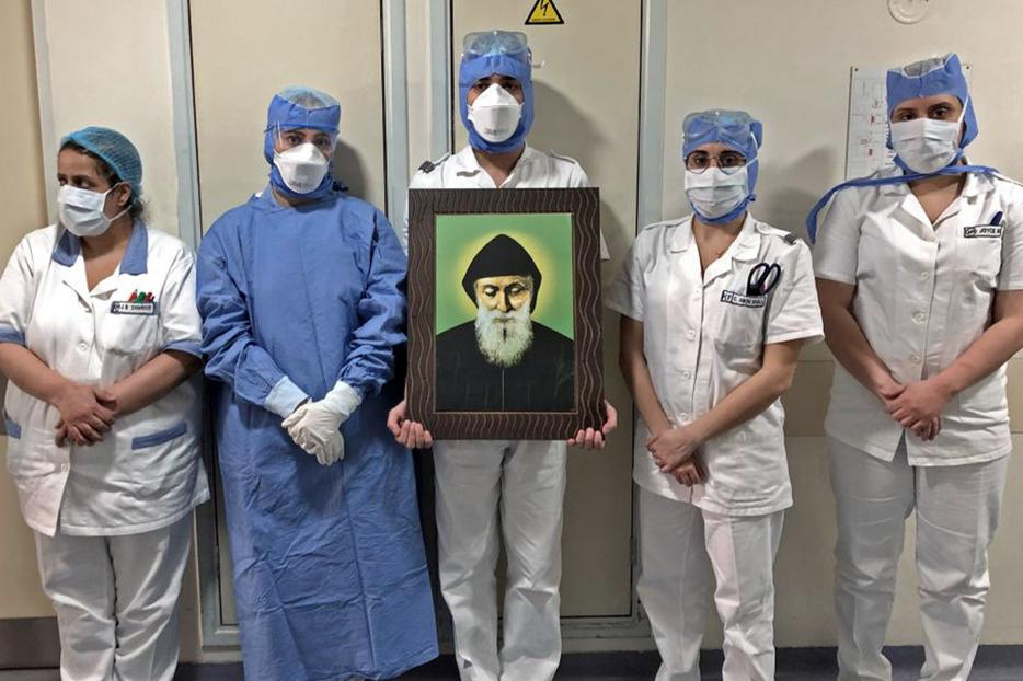 In a picture taken by a nurse on April 9, 2020, at the Hôtel Dieu de France Hospital in Beirut, Lebanon, medical workers carry a picture of St. Charbel in the COVID-19 section of the hospital.