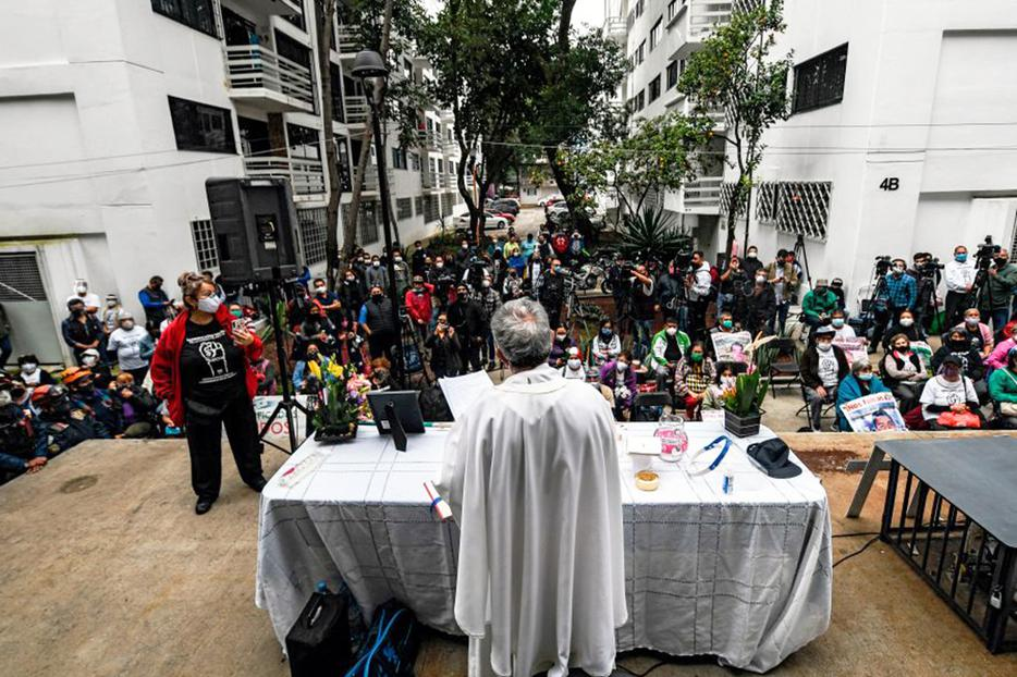 A priest offers Mass at the Tlalpan multifamily complex on the third anniversary of the earthquake that destroyed part of its buildings in Mexico City, on Sept. 19, 2020.