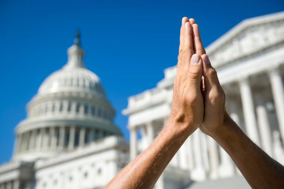 Hands in prayer before the U.S. Capitol building in Washington D.C.