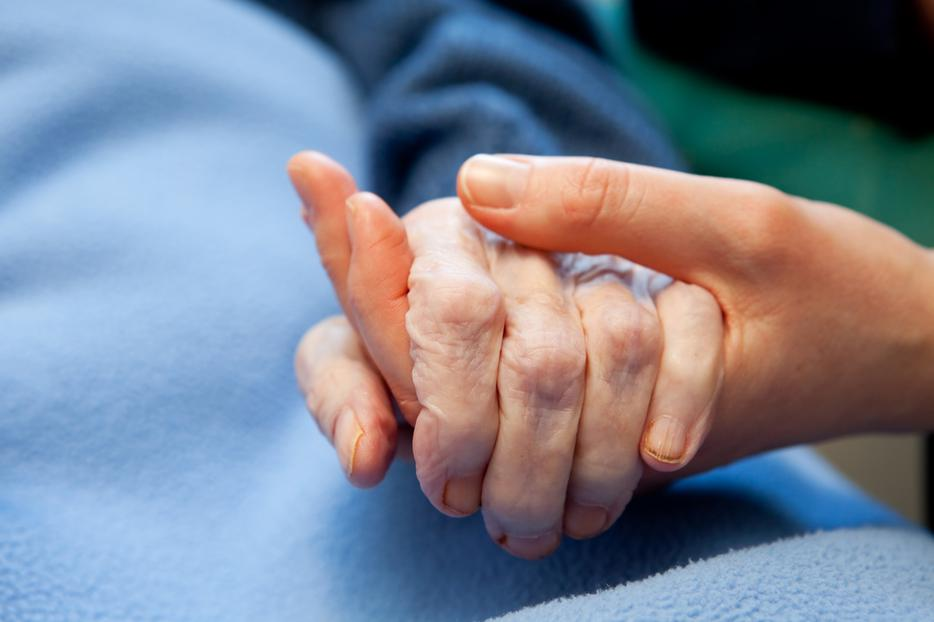 A woman holding the hand of an elderly person at a hospital.