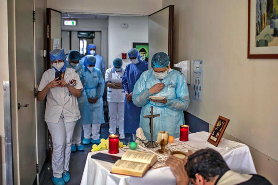 A picture taken by a nurse on May 8 at the Hôtel Dieu de France Hospital in Beirut, Lebanon, shows health workers gathered to attend a Mass offered by a priest in the COVID-19 section of the hospital.