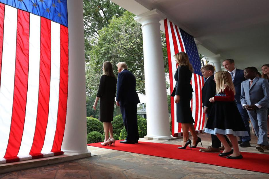 President Donald Trump Judge Amy Coney Barrett walk into the White House Rose Garden on Saturday with first lady Melania Trump and Barrett's family to present Barrett as his nominee to the Supreme Court.
