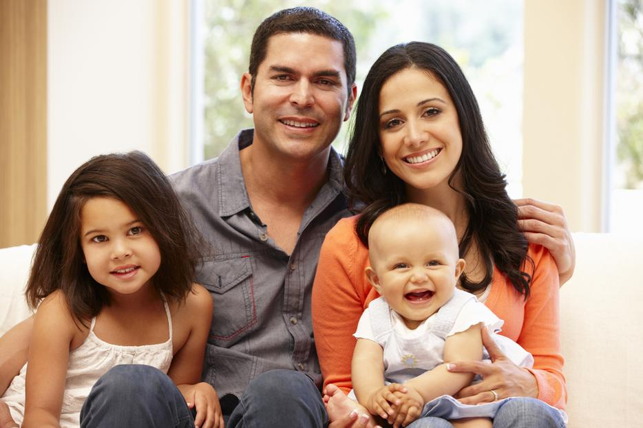 Hispanic family of four poses with their young baby.