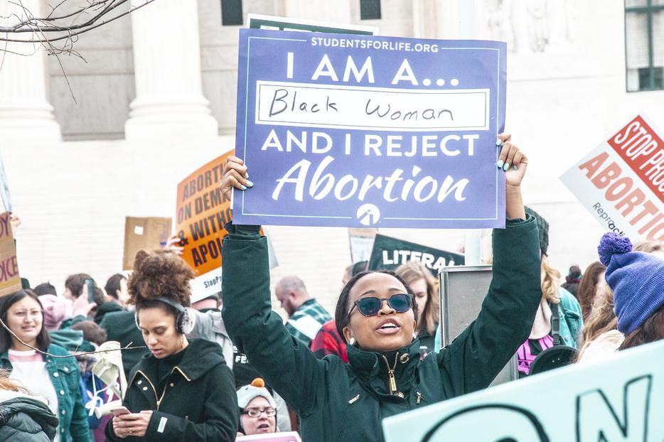 'I Am a Black Woman and I Reject Abortion,' proclaims a sign held aloft by a participant at the annual March for Life.