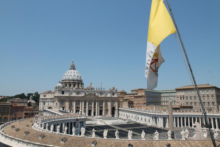 The flag of Vatican City with St. Peter's Basilica in the background. This particular flag with vertical bands of gold and white with the coat of arms of the Holy See was adopted on June 7, 1929.