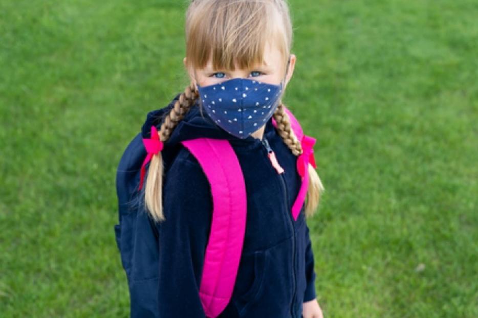 Young Catholic school girl wears a mask amid the coronavirus pandemic.