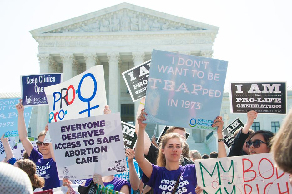 The pro-life community holds signs amid pro-abortion advocates awaiting the Supreme Court's ruling on abortion access in front of the Supreme Court in Washington, DC on June 27, 2016