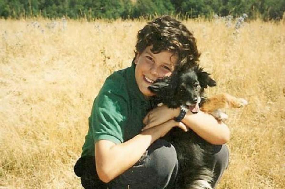 A young Carlo Acutis holds his pet dog.