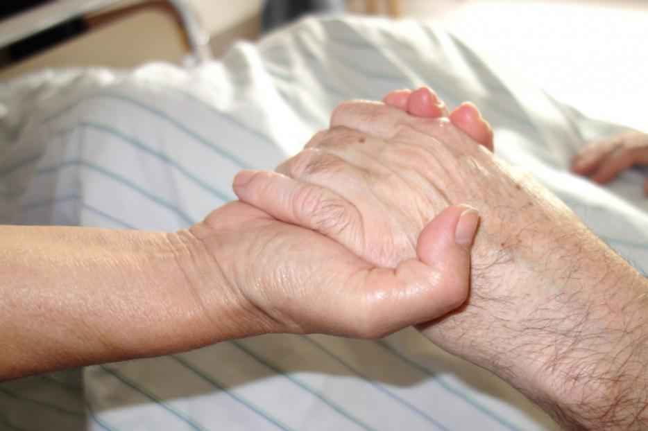 A daughter holds her mother's hand in the hospital.