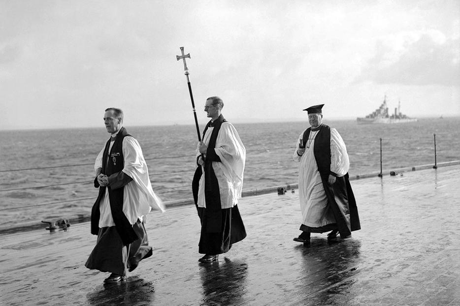 The Chaplain of the Fleet (L) and the Archbishop of Canterbury, William Temple (R) process with a crucifer for an Anglican service on the quarterdeck of HMS King George V at Scapa Flow, in the Orkney Islands, Scotland, during World War II. After the war, both institutions would undergo a steep decline in prestige and power, with the Royal Navy dropping from more than 2,000 ships to fewer than 80 operational commissioned ships in 2020, and Anglican churchgoing currently hovering around 1% of the U.K. population.