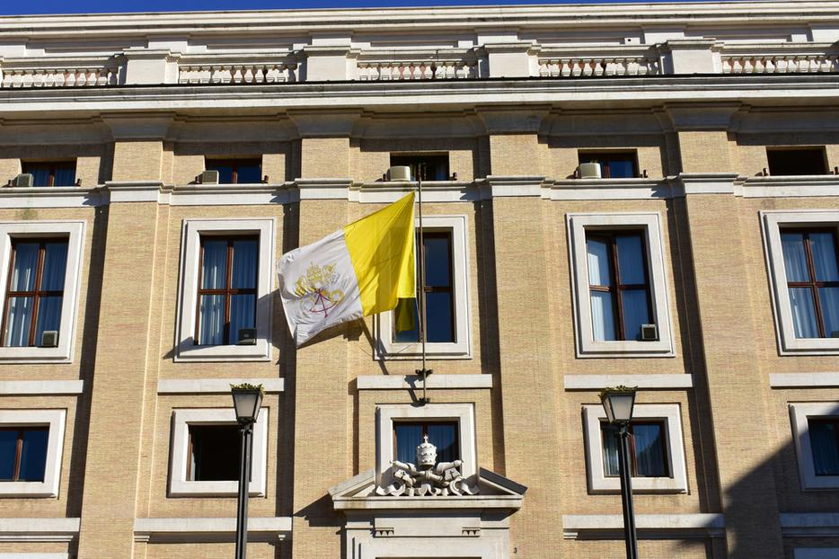 Building with the flag of the Vatican and the Vatican Coat of Arms in Vatican City.