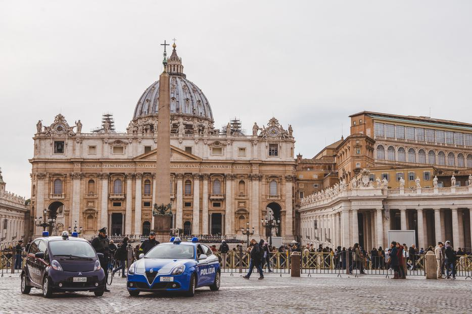 A crowd of people and police cars in  front of St. Peter's Square.