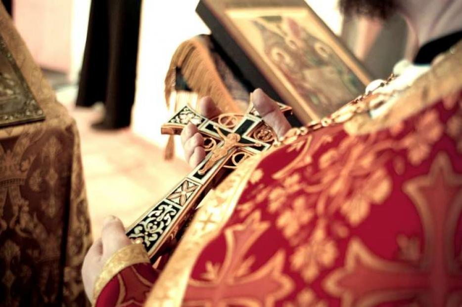 Byzantine priest holds a crucifix.