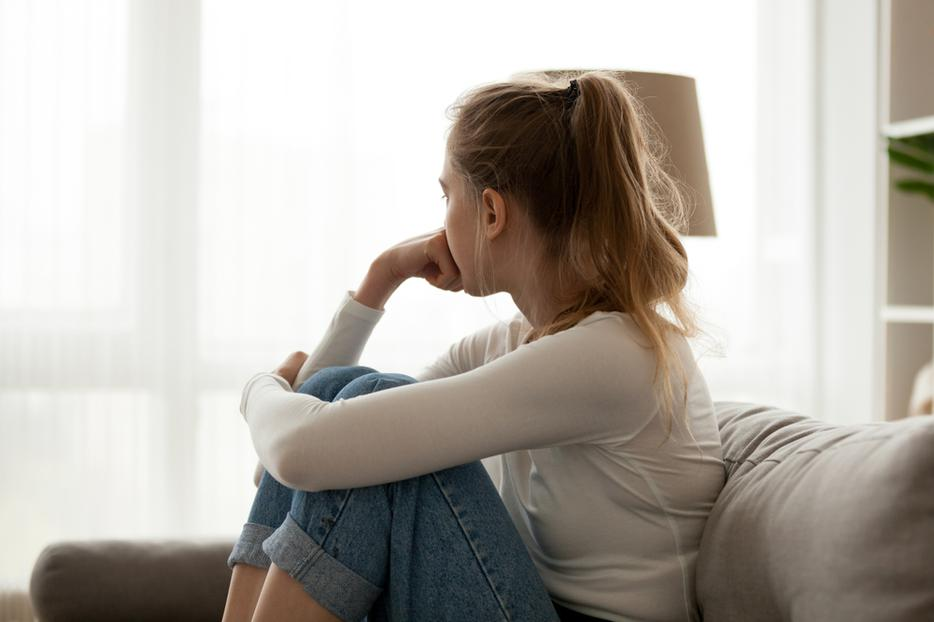 A young woman sits looking out the window contemplating an abortion.