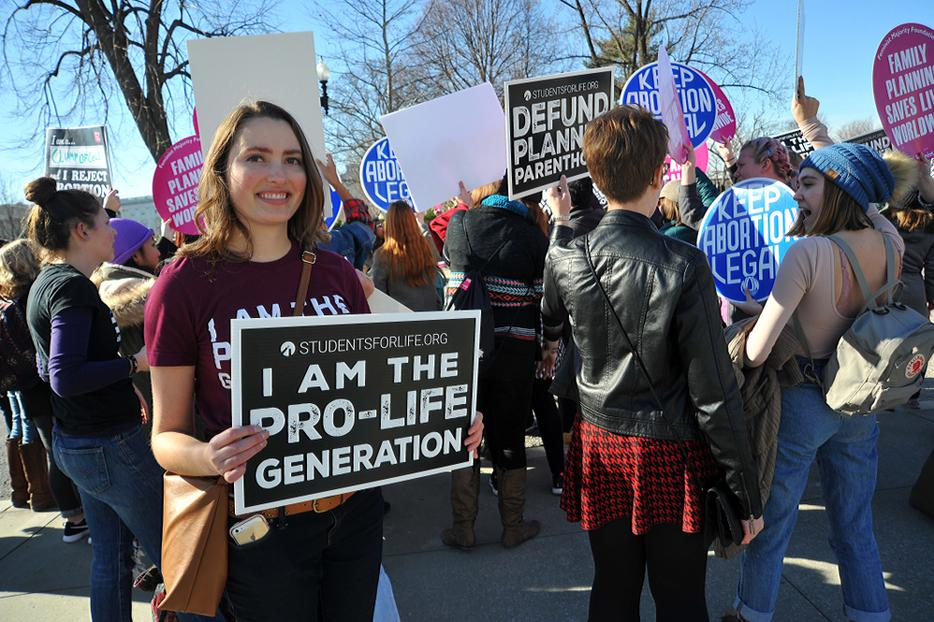 A young woman holds a pro-life sign near the US Supreme Court during the March For Life.