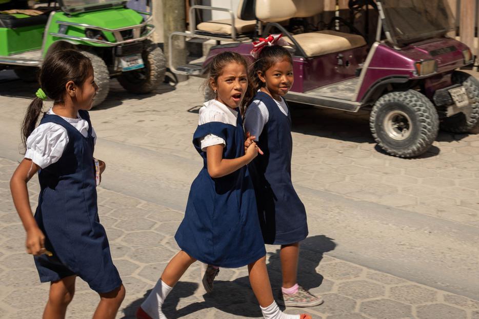 Three local Belizean girls crossing the street during lunch break in Catholic school San Pedro, Belize on November, 15, 2019.
