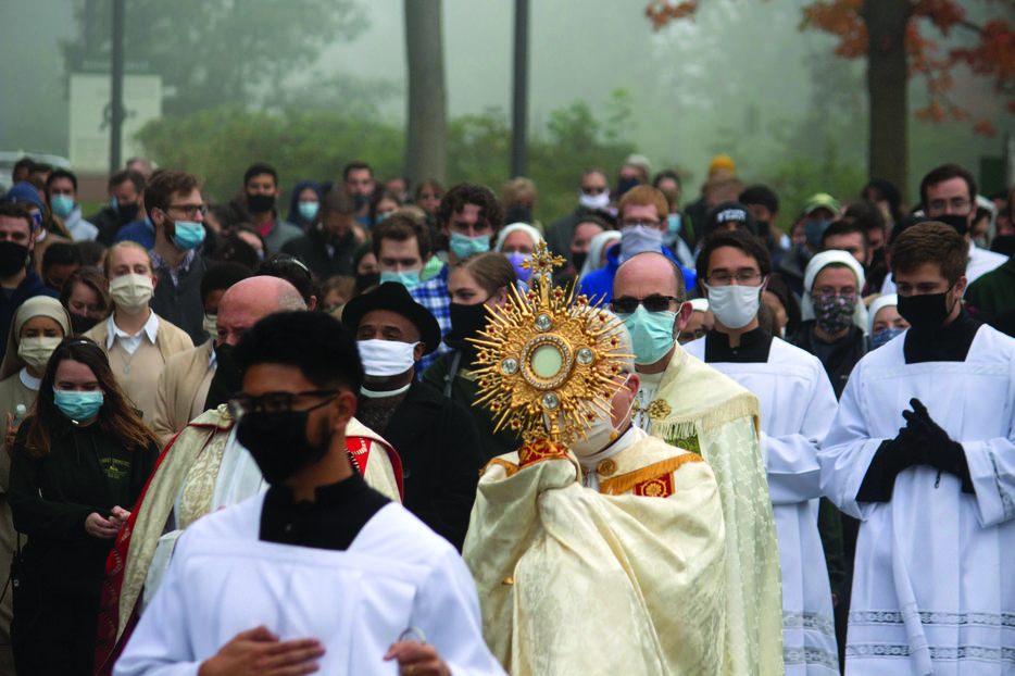 Bishop Jeffrey Montforton of Steubenville, Ohio, carrying a monstrance containing the Blessed Sacrament, leads a procession from the Franciscan University campus through downtown Steubenville Oct. 3 as part of the nationwide 'Unite the Nation' events.