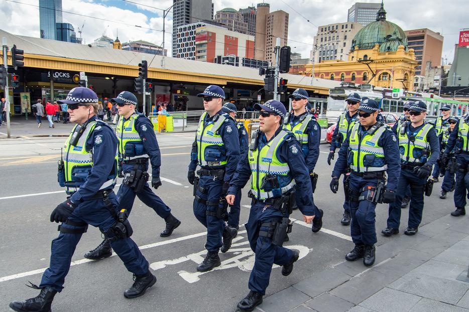 Victoria Police officers marching in formation along Swanston Street, between Flinders Street Station and Federation Square.