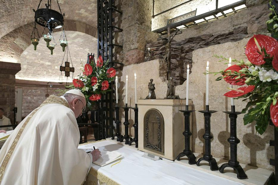 Pope Francis signs his new encyclical 'Fratelli tutti'after celebrating Mass at the tomb of St. Francis inside Assisi's Basilica of St. Francis, Oct. 3, 2020.