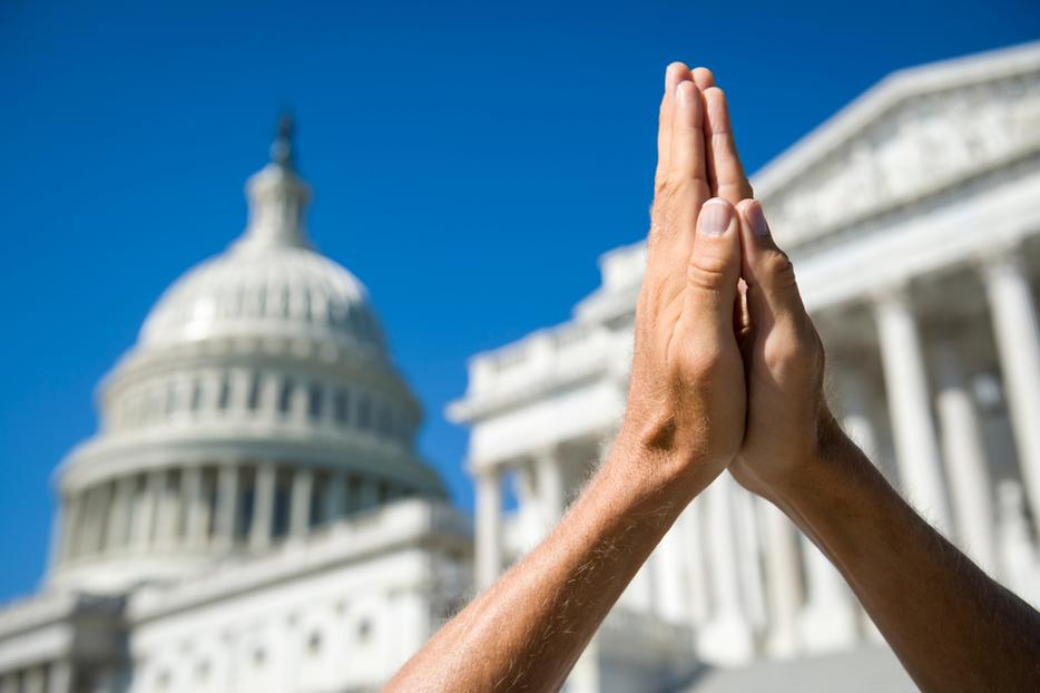 Hands held together in prayer in front of the Capitol building and Supreme Court in Washington, D.C.