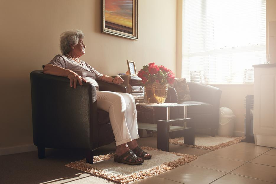 An elderly woman sits alone in her room.