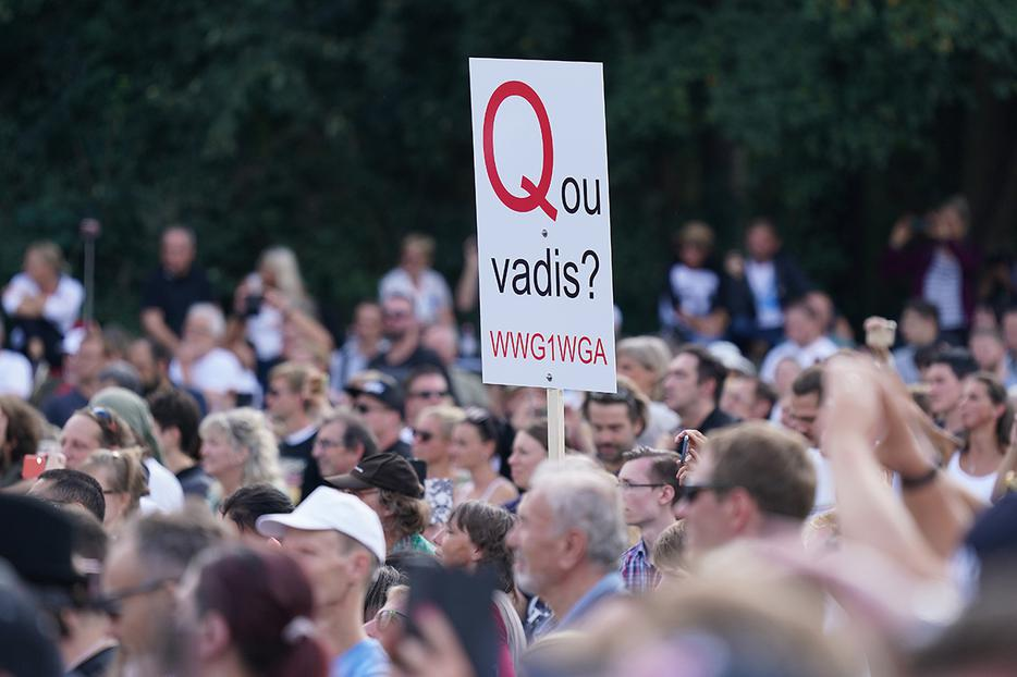 "A QAnon supporter, holding a misspelled ""Quo Vadis"" sign, attends a rally protesting coronavirus-related restrictions at the Victory Column in Berlin, Germany, on Aug. 29."