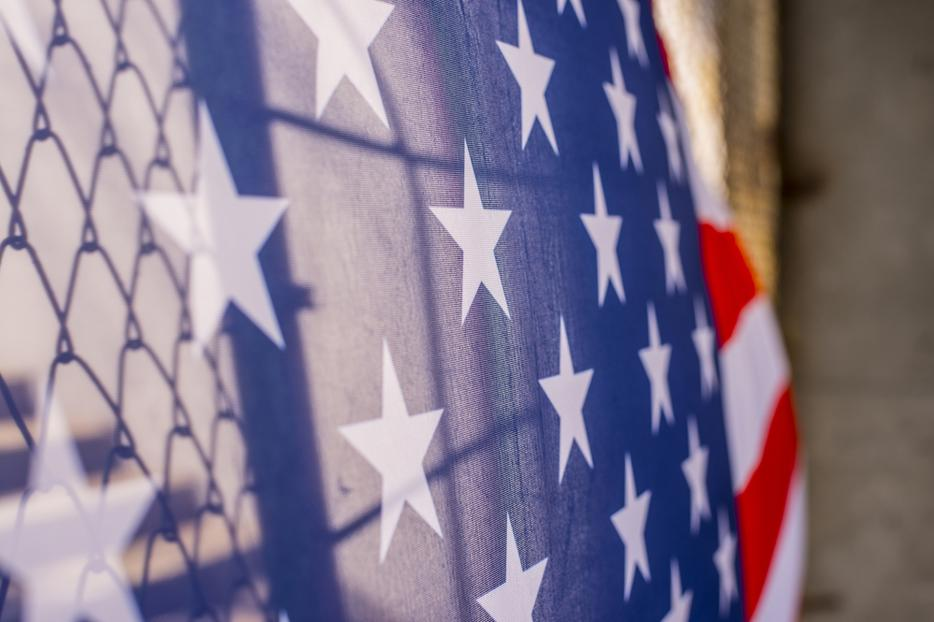 An American flag is shown draped over a border fence.