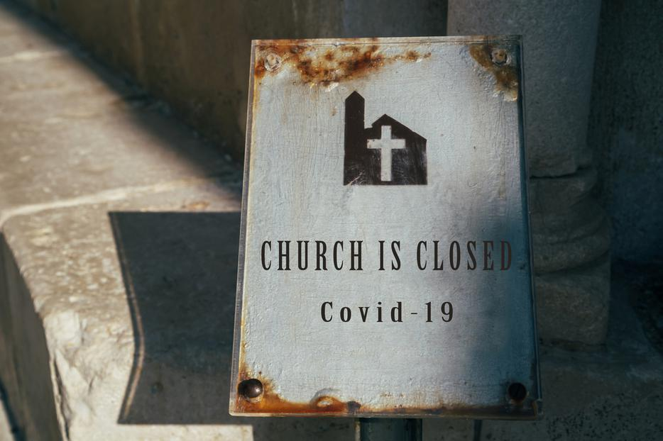 A sign outside a parish indicating the church is closed due to COVID-19.