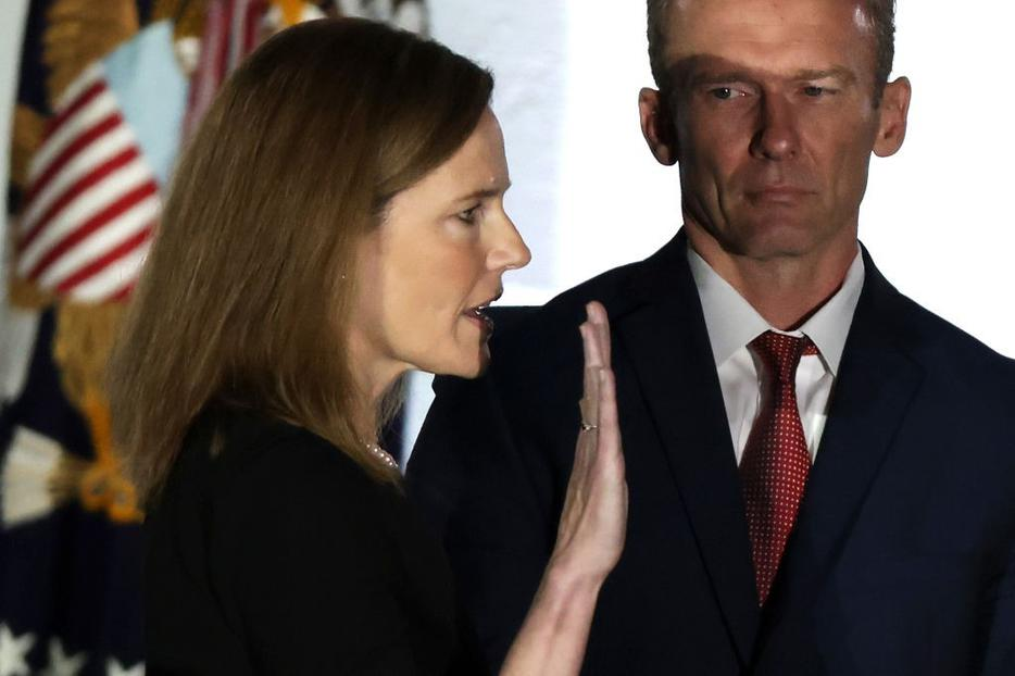 Judge Amy Coney Barrett is sworn in as a U.S. Supreme Court associate justice during a ceremony on the South Lawn of the White House Oct. 26. Her husband, Jesse, looks on.