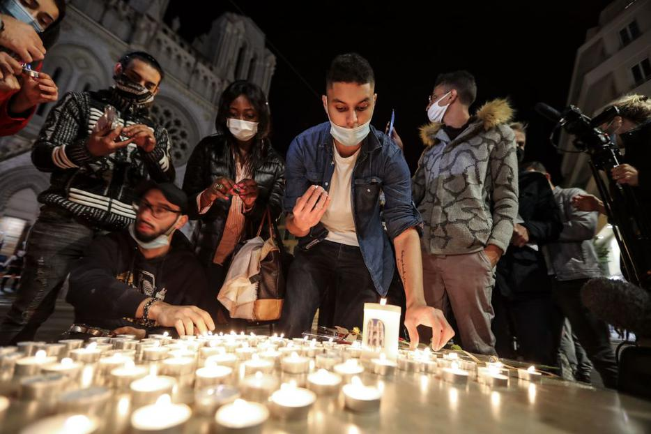 People lights candle outside the Notre-Dame de l'Assomption Basilica in Nice on October 29, 2020 in tribute to the three victims of a knife attacker, cutting the throat of at least one woman, inside the church of the French Riviera city.