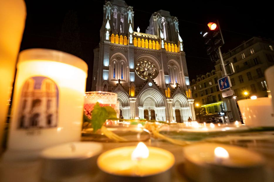 People pay tribute at night in front of Notre Dame Basilica on October 29, 2020 in Nice, France. A man armed with a knife fatally attacked people in the church, located in the heart of the city.
