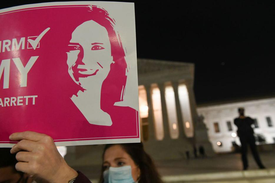 A pro-life activist and a supporter of naming Judge Amy Coney Barrett as a Supreme Court Justice, holds a sign in front of the Supreme Court building in Washington, DC on October 26, 2020.
