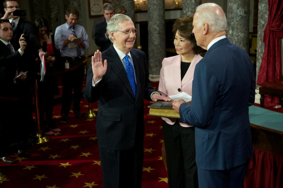 Senator Mitch McConnell with his wife Elaine Chao holding the bible is sworn in by Vice-President Joseph Biden on January 6, 2015.