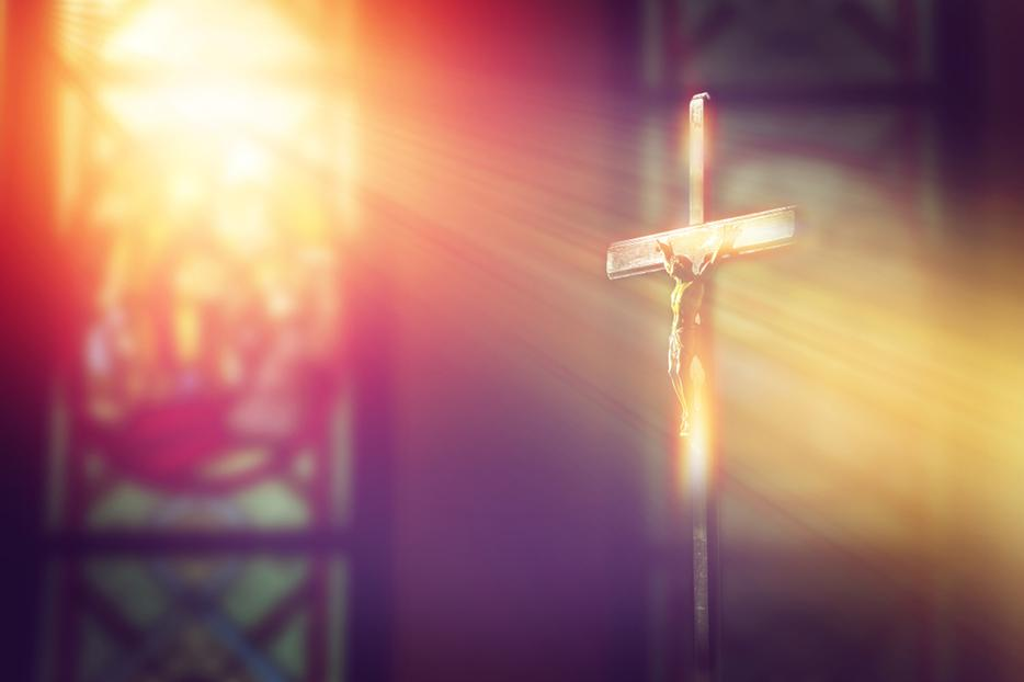 Rays of light from a stained glass window shine down on a crucifix inside a Catholic church.