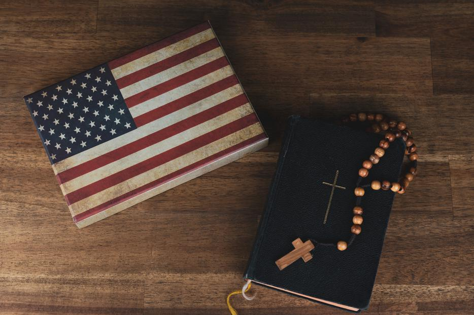 A table holds an American flag next to a Bible with a Rosary resting on it.