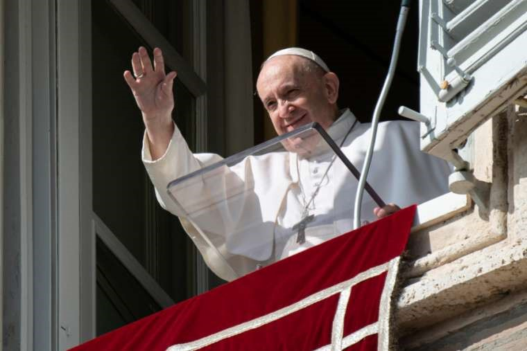 Pope Francis waves to pilgrims in St. Peter's Square during the Angelus on Oct. 26.
