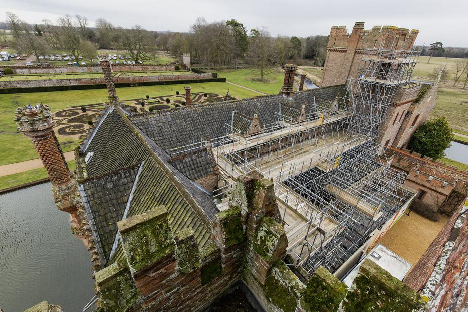 Oxburgh Hall is covered in scaffolding during building work to replace the roof of the moated manor house. Catholic artifacts have been discovered through the process.