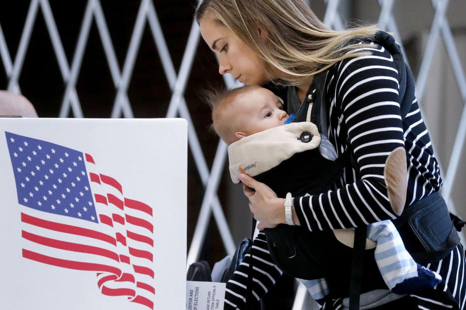 Voter Izzi Buckles holds her son, Rowan, as she marks her ballot in a polling place at Roosevelt High School on Nov. 3 in Des Moines, Iowa. The election results are still not settled, and Catholics are urged to keep a Christ-focused perspective in these challenging times.