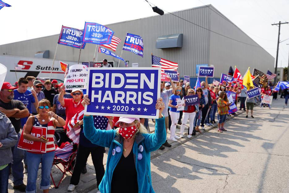Voters hold signs during a rally outside of an aluminum foundry in Manitowoc, Wisconsin on September 21th, 2020.