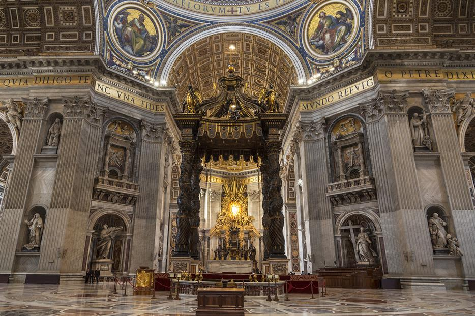 The interior of St. Peter's Basilica in Vatican City with a Baroque canopy over the altar.