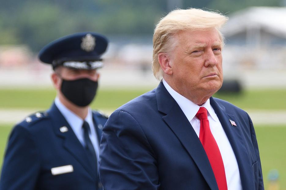 President Donald Trump walks  with Air Force Major General John P. Healy in the background wearing a face mask at Dobbins Air Reserve Base.