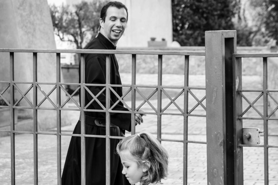 A priest smiles at a child playing just outside the first Passionist monastery in Monte Argentario, Italy.