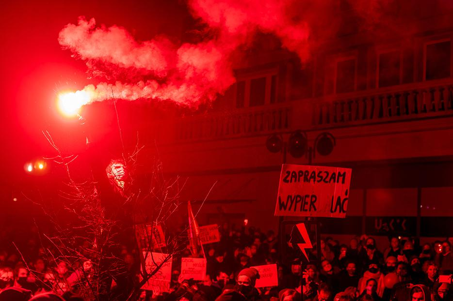 A demonstrator lights a flare as he takes part in a pro-abortion protest in central Warsaw on Nov. 18.