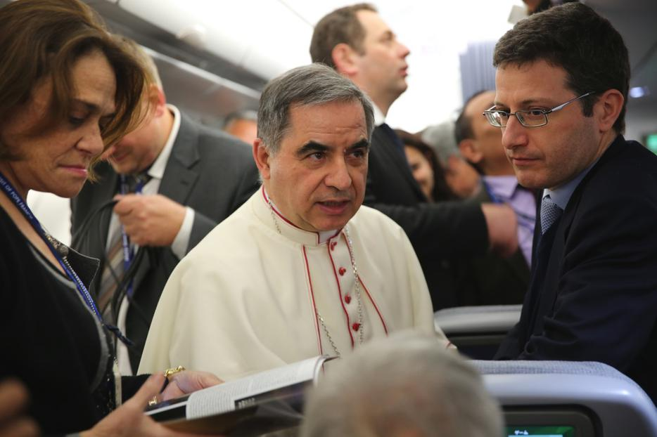 Archbishop Giovanni Angelo Becciu speaks with journalists aboard the papal flight to Colombo, Sri Lanka on Jan. 12, 2015.