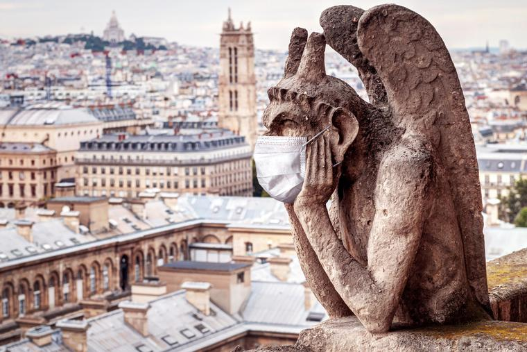 Gargoyle sits atop Notre Dame in Paris wearing a face mask.