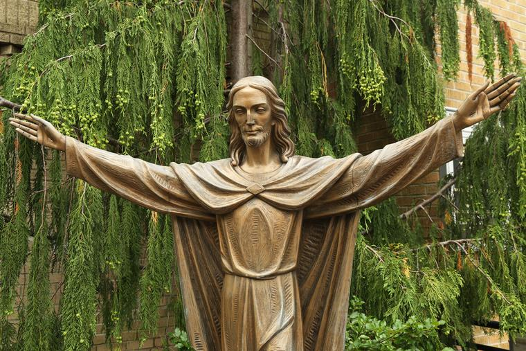 Bronze Statue of Jesus Christ in front of Church of Mary Queen of Haven in Brooklyn on July 13, 2013.