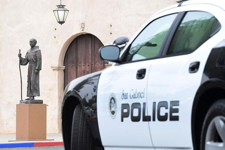 A police vehicle is seen parked near a statue of Father Junípero Serra in front of the San Gabriel Mission in San Gabriel, California, on June 21, 2020.