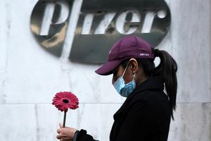 A woman walks by Pfizer's New York headquarters on Nov. 16 as New York City tries to contain a spike in COVID-19 cases.